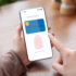 Hands holding smartphone with mobile payment app open and fingerprint; copyright: Prostock-studio