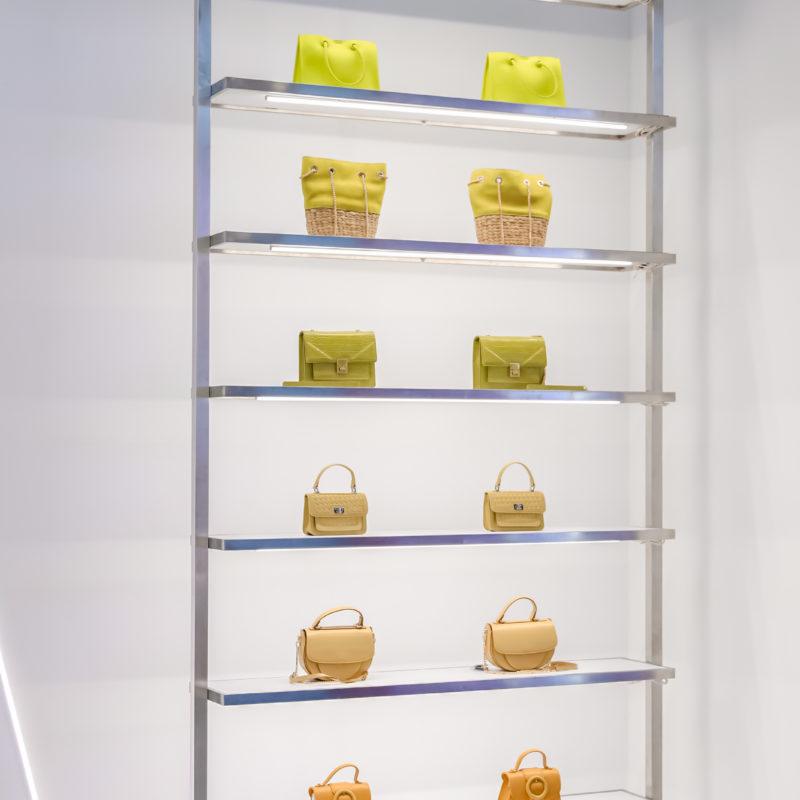 A high narrow metal shelf with handbags