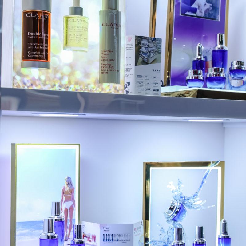 Perfume bottles in an illuminated shelf