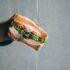 Hand, die ein Sandwich in die Kamera hält; copyright: unsplash