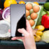A person holds a smartphone over a box of fresh food