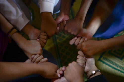 Verschiedene Hände, die sich alle in einem Kreis am Daumen festhalten