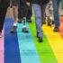 Beine verschiedener Menschen, die über einen regenbogenfarbenen Boden gehen