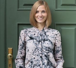 Blonde Frau steht vor dunkelgrüner Tür und lächelt in die Kamera; copyright: nebenan.de