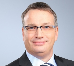 Mann im Anzug, grauen Haaren und Brille lächelt in die Kamera