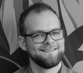 Schwarz-Weiß-Foto von Alexander Schneider - Mann mit Brille und Bart lächelt schräg in dien Kamera