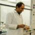 A scientist in a laboratory holding a Petri dish and a pipette