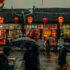 Passanten auf einer Straße in China vor Shopfronts mit Lampions