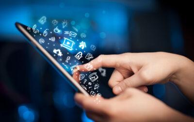 Eine hand bedient ein Tablet mit virtuellen Icons aus der digitalen Welt darüber