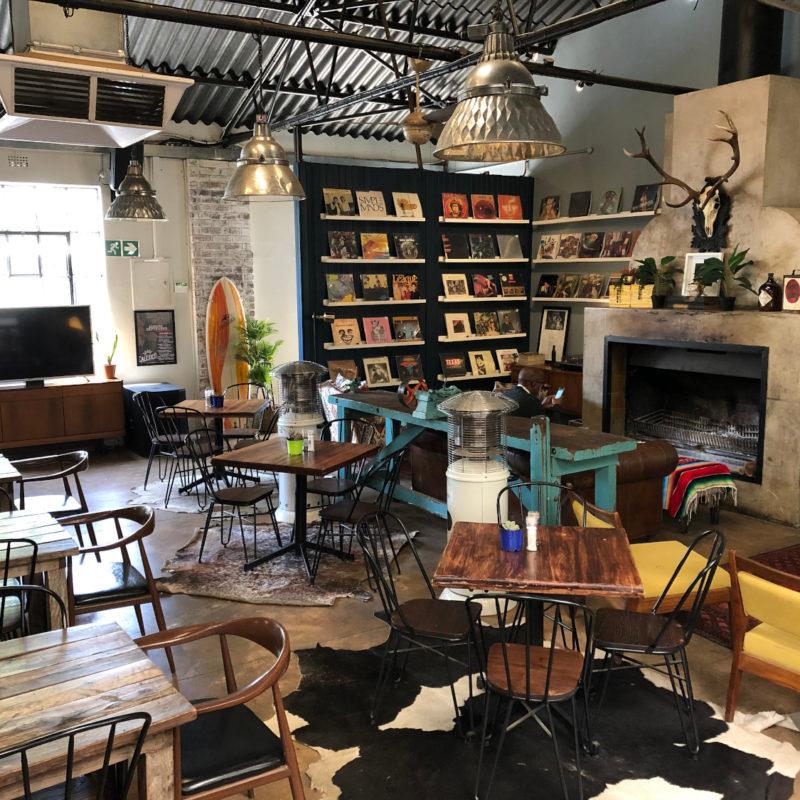 Blick in ein Cafe mit Tischen und Schallplatten im Regal