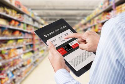 Ein Mann hält in einem Supermarkt zwischen Regalen ein Tablet PC in der Hand