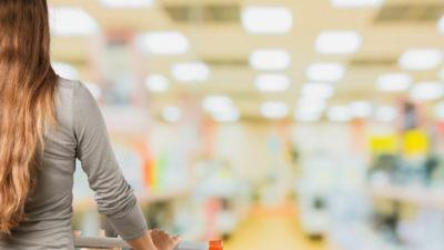 Eine Frau im Supermarkt schiebt einen Einkaufswagen, von hinten fotografiert