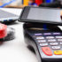 Hand holding smartphone close to a payment terminal