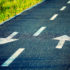 A paved road with two lanes and white arrows in both directions; copyright: PantherMedia/Demachy