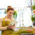 Woman working in a flower store holding a tablet pc