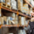 Woman with a headset in a warehouse full of packages