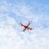 Orange drone with four rotos agianst blue sky; copyright: