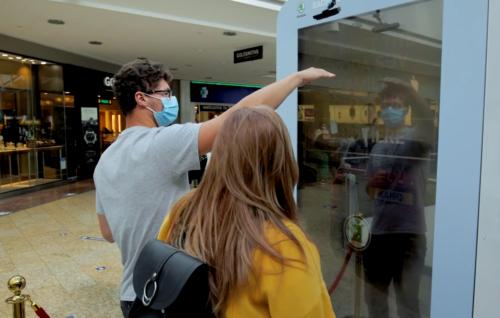 Ein Mann und eine Frau vor einem großen Bildschirm, der mit seinen Händen gestikuliert