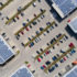 shopping center with solar photovoltaic panels on the roofs and a parking lot with cars, aerial view.