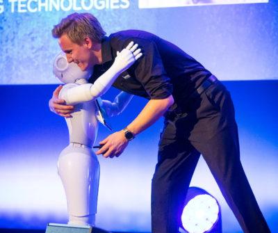 Junger Mann umarmt Roboter Pepper auf einer Bühne; copyright: Humanizing Technologies