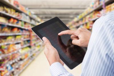 Hände, die ein Tablet im Supermarkt bedienen; copyright: PantherMedia / Shutter_M