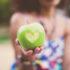 Ein Mädchen hält einen grünen Apfel, in den ein Herz geschnitzt wurde