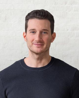 Ein junger Mann mit kurzen dunklen Haaren