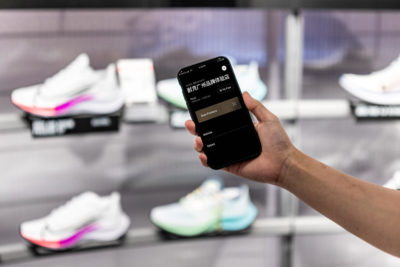 hand holding a smartphone with nike shoes in the background