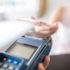 Frauenhand bezahlt mit Smartphone am POS-Terminal