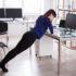 Frau drückt sich an Schreibtisch hoch