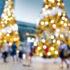 Verschwundene Hintergrundbild von defokussierten Weihnachtsdekorationen im Freien mit bunten Lichtern und Menschenmassen in belebter Stadtstraße in der Nacht
