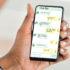 Frauenhände, die ein Smartphone mit geöffneten Chatfenstern halten