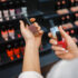 Woman takes lipstick from shelf in cosmetics store