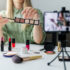 Makeup beauty fashion blogger influencer recording video showcasing cosmetics on social media at home