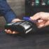 Eine Person bezahlt kontaktlos mit einer Bankkarte