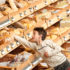 Young boy reaching into one of many bread baskets in a supermarket; copyright: panthermedia.net/CandyBox Images