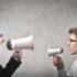 Zwei Männer, die sich mit Megaphonen anschreien