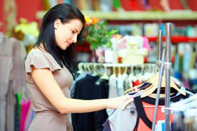 Frau schaut sich Kleider im Geschäft an.