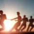 Silhouettes of men in the rising sun having a tug war; copyright: panthermedia.net/Iurii