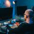 Zwei Leute arbeiten an PCs in dunklem Raum; copyright: panthermedia.net / VitalikRadko
