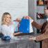 Sales woman handing customer some bags at cash register; copyright: panthermedia.net/IgorVetushko
