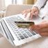 Nahaufnahme Frau Hände halten eine Kreditkarte und mit Computer