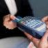 Hand, die Ihre Karte in ein Bezahl-Terminal schiebt