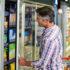 Mann im karierten Hemd, der im Supermarkt etwas aus der Tiefkühlabteilung nimmt.