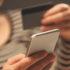 Frau bezahlt mit ihrem Smartphone und hält ihre EC-Karte in der anderen Hand