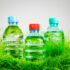 three filled bottles stand in the grass