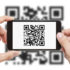 Two hands holding a smartphone that scans a QR code
