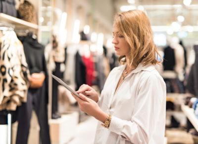 Eine junge blonde Frau steht in einem Bekleidungsgeschäft mit einem Tablet PC in der Hand