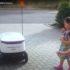 Three children standing next to a white self-driving robot