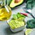 Grüne Guacamole in einer viereckihen weißen Schale dekoriert mit einer Scheibe Zitrone und Minzblättern